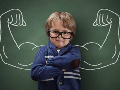 Strong man child showing bicep muscles concept for strength, confidence or defence from bullying