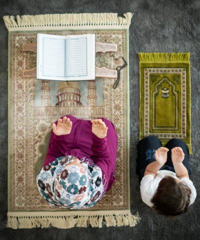 Muslim family in living room praying and reading Koran